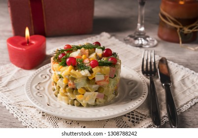 Olivier salad on a white plate and cutlery on the table.