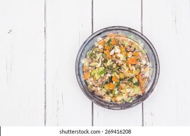 Olivier traditioneller Salat in einem schwarzen Kunststoffbehälter einzeln auf weißem Holzhintergrund.