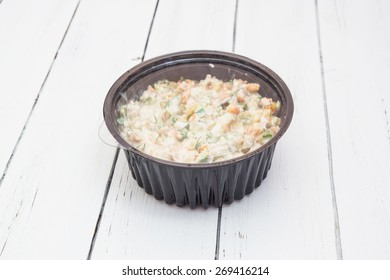Olivier traditional salad with sour cream or mayonnaise in a black plastic container isolated on a white wooden background.