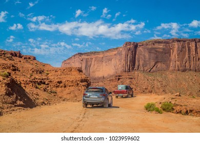 Oljato-Monument Valley, Arizona / USA - June 28 2017: tourist cars on a dusty dirt road in the Monument Valley, Utah. Tour to the landmarks of the Wild West USA. Navajo tribal park