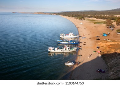 OLKHON, RUSSIA-JULY 27, 2010. Several swimmers, sunbathing or walking in one of the beaches Olkhon Island on Lake Baikal. The beach also serves as a port for some boats on July 27,2010