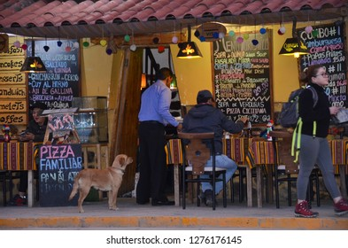 OLLANTAYTAMBO / PERU, August 15, 2018 : A dog watches dinner being served in a restaurant in the main square of Ollantaytambo.