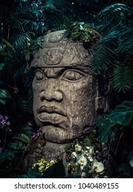 Olmec sculpture carved from stone. Mayan symbol - Big stone head statue in a jungle