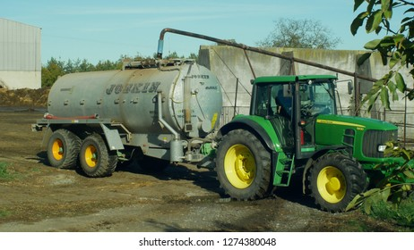 OLOMOUC, CZECH REPUBLIC, AUGUST 21, 2018: Tractor John Deere special trailer spreading fertilizer of slurry on field farming, tanking of liquid dung healing from cows, fertilization slurry important