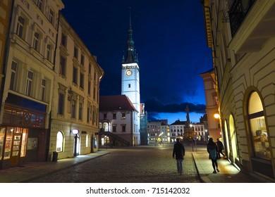 OLOMOUC, CZECH REPUBLIC – FEBRUARY 24, 2017: Pedestrians walk down a cobblestone street in Olomouc, Czech Republic at twilight view toward the Town Hall and Holy Trinity Column.