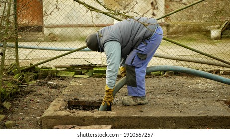OLOMOUC, CZECH REPUBLIC, JANUARY, 20, 2021: Cesspool septic emptying pumping into pipe tank truck suction hose under pressure. people worker houses village, sump contains pollution sludge sewage water