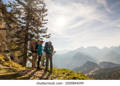 Olseva / Slovenia - November 4 2017: Three hikers are looking at the map and admiring the view over the valley in Olseva, Slovenia