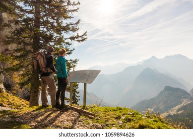 Olseva / Slovenia - November 4 2017: Two hikers are looking at the map and admiring the view over the valley in Olseva, Slovenia