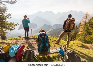 Olseva / Slovenia - November 4 2017:  Three hikers are resting and enjoying the view over the valley in Olseva, Slovenia