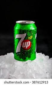 OLSZTYN, POLAND - February 16 ,2016 : 7 Up can splashed with water on ice cubes, on black background, product shot