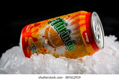 OLSZTYN, POLAND - February 16 ,2016 : Mirinda can splashed with water on ice cubes, on black background, product shot