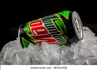 OLSZTYN, POLAND - February 16 ,2016 : Mountain Dew can splashed with water on ice cubes, on black background, product shot