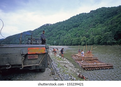 OLT, TRANSYLVANIA, ROMANIA - JUNE 18: rafter on Olt river drive wooden raft on June 18, 2000 in Olt, Transylvania, Romania. Rafting logs was traditional way of transport logs.