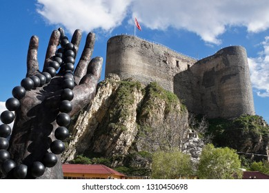 OLTU, TURKEY — MAY 9, 2011. A sculpture of a hand holding a string of black amber beads rises in front of Oltu Castle, flying the Turkish flag, high on a hill on a sunny day with blue sky and clouds.