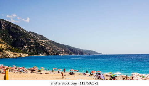 Oludeniz Beach (Blue Lagoon), Fethiye / Mugla, Turkey - 29.06.2018: The landscape of the beach and mountains on background. People lying on sand and swimming. Breathtaking turquoise sea / yellow sand.