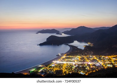 Oludeniz landscape beautiful sunset lagoon in sea view of beach, Turkey. With city lights, beach and mountain is best touristic destination of Fethiye.