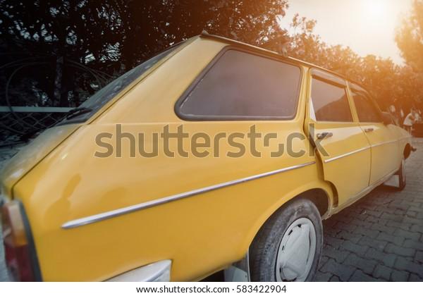 Oludeniz, Turkey, April 28, 2016: Yellow car parked on a city street, sunny