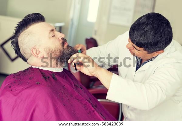 Oludeniz, Turkey, April 28, 2016: Male barber cuts the beard of a adult man with a mohawk. Toned