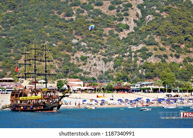 OLUDENIZ, TURKEY - September 2014: The beach veiw of Oludeniz, Turkey. The paraglider landing on the beach and pirate excursion tourist ship on the beach in Oludeniz, Turkey