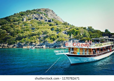 OLUDENIZ, TURKEY - September 2014: Excursion ships and islands in front of azure water of the Mediterranean sea, Oludeniz, Turkey