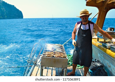 OLUDENIZ, TURKEY - September 2014: The fisherman cooks the grilled fresh fish during the sea trip in Oludeniz, Turkey