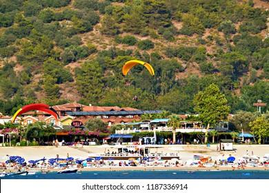 OLUDENIZ, TURKEY - September 2014: The paraglider landing on the beach in Oludeniz, Turkey