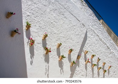 Olvera is a white village (pueblo blanco) in Sierra de Grazalema, Cadiz province, Andalucia, Spain - typical vases hanging on the wall with carnations