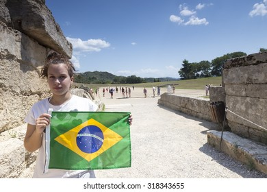 Olympia, Greece- August 9, 2015: Girl holds the Brazilian flag for the next Olympics at Olympia birthplace of the Olympic games, in Greece.