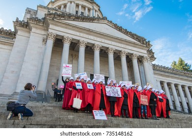 OLYMPIA, WA, OCTOBER 14, 2017: Men and women dressed in Handmaid's Tale costumes rally on the steps of Washington's state capitol to protest Trump administration policies; part of a 50 state movement.