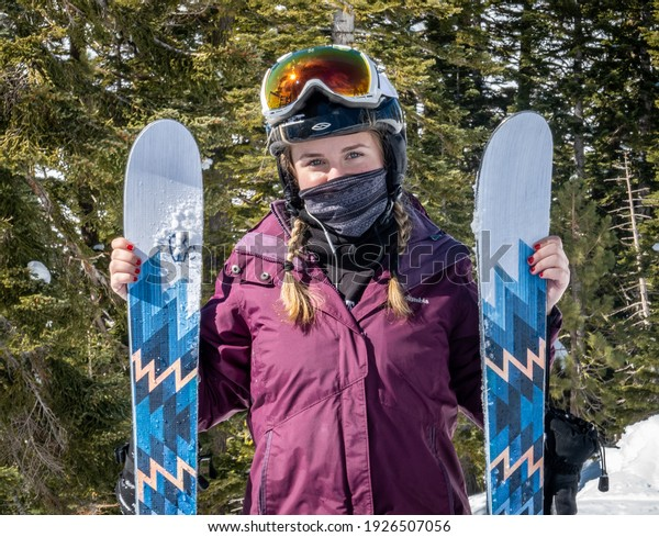 Olympic Valley, California - February 22, 2021: A young woman skier wears a face covering mask during the Covid 19 coronavirus global pandemic at the Squa Valley ski resort.