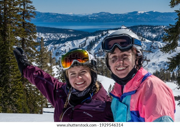 Olympic Valley, California - February 24, 2021: Two young women enjoy a day of skiing at the Squa Valley Ski Resort, with a view of Lake Tahoe in the background.
