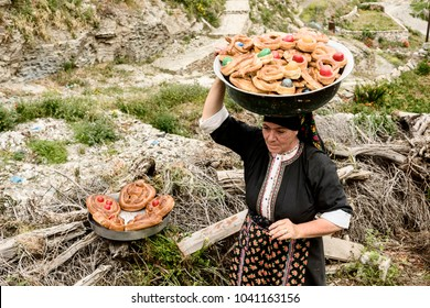 OLYMPOS, KARPATHOS island – april 23, 2008 : Easter, a woman picks up all the buns decorated with a red egg
