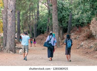 OLYMPOS, TURKEY – SEPTEMBER 28, 2011: Rear view of people walking on a footpath in between pine trees in Olympos, Turkey