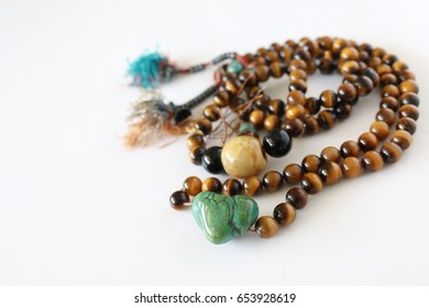 Om mala with  green heart bead on white background , Tibetan mala beads for prayer