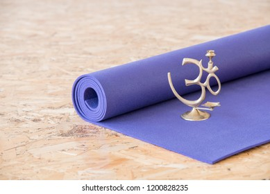 Om meditation sign on a purple yoga mat in the training room