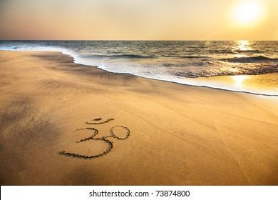 Om symbol on the sand at the beach near the ocean