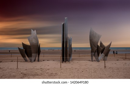 """Omaha Beach, France - 20 August 2017:  sunset over the monument """"Les Braves"""" (The Braves), on the famous beaches of Normandy"""
