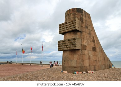OMAHA BEACH, FRANCE - AUGUST 2, 2014: Tourists visit the D-day monument on Omaha beach in Normandy, France, on August 2, 2014