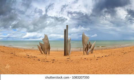 Omaha Beach, France - August 2, 2014: Beautiful panorama of WWII monument Les Braves, on the center of Omaha Beach in Normandy, France, with clouds in summer, on August 2, 2014