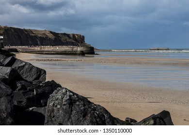 Omaha Beach, Juno Beach - spring coastline of one of the D-Day beaches of Normandy, France. Seashore, rocks and coudy sky
