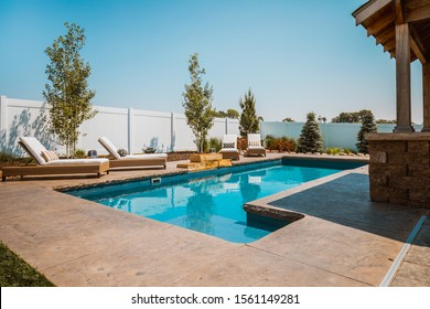 Omaha, Nebraska / USA - 08/20/2019: Luxury backyard pool and patio landscaping in the summer with loungers and a pergola in Nebraska, USA