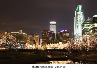 Omaha Trees lit up in white Lights in the city with reflection in the water.