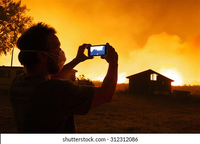 Omak, WA, USA August 19, 2015: Onlooker takes video with cell phone as flames rapidly approach buildings and property.  Okanogan Complex Fire, Washington state's largest, most destructive fire ever