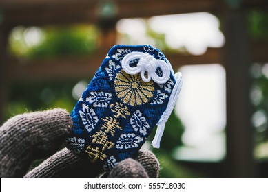 Omamori Japanese lucky charm holding in a hand in cloudy day. Japanese word in picture says : Success in Education