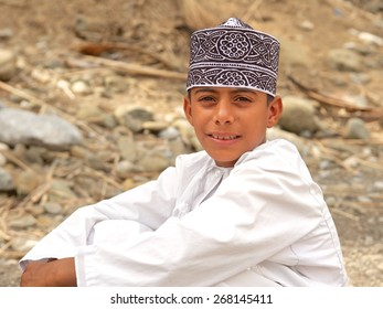 OMAN - FEBRUARY 1, 2008: An Omani boy wearing a kummah (traditional cap) relaxes in a wadi below his grandfather's date plantation in the desert interior of the Sultanate of Oman.