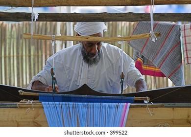 oman man operating machine making clothes