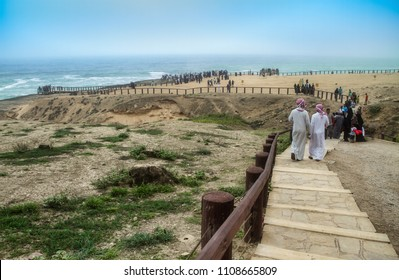 Oman, Salalah, Mughsail beach, visitors at viewpoint below dramatic cliffs in july 21, 2011
