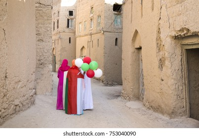 omani ladies wearing omani flags and baloons with national colors, in celebration of national day