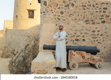 omani man standing with traditional cannon at mutra fort