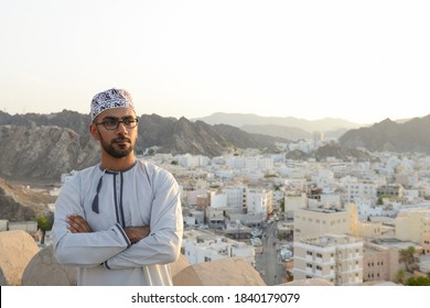 omani man with traditional house in the background